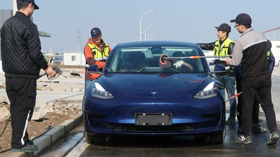 Arbeiter in Teslas neuer Fabrik in Shanghai reinigen ein Model 3