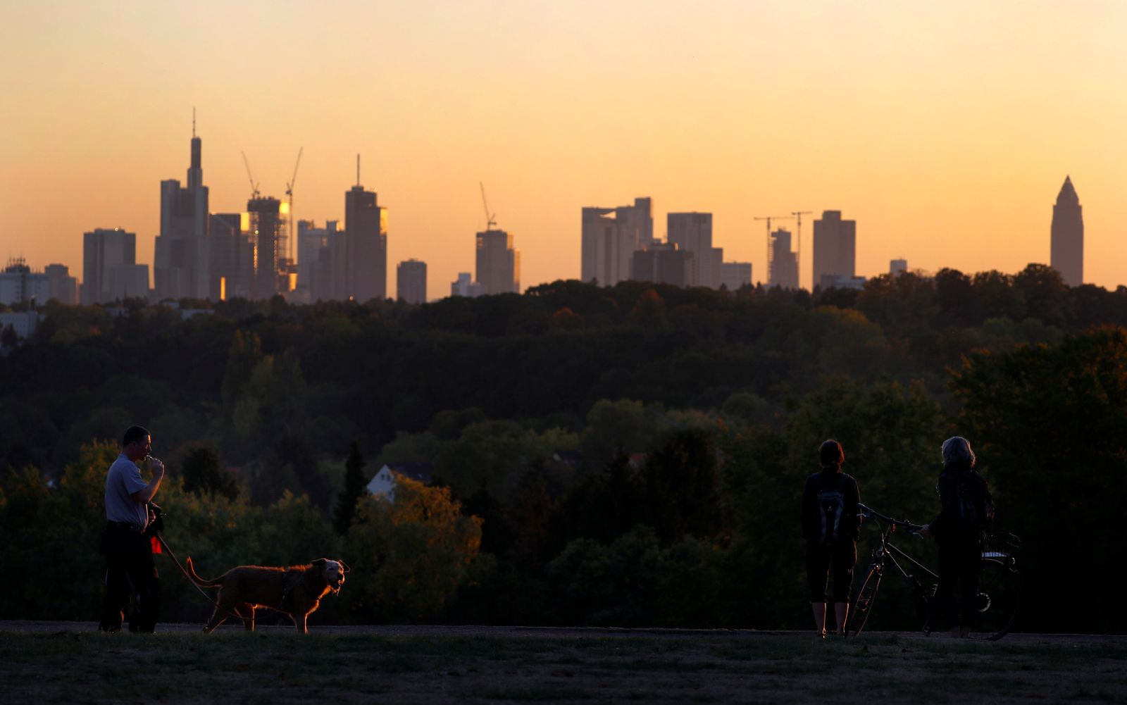 People enjoy the view of the skyline with its financial district ion early evening in Frankfurt