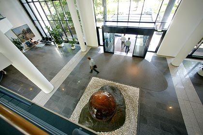 """SAP-Fazit von Hadi Teherani: """"Ein gesichtsloser Komplex mit altbackenen Schmuckelementen wie aus dem Anker-Steinbaukasten. Ein Zweckbau, der nur sein Logo in den Himmel halten kann. Der Rest ist Symmetrie und Schweigen."""""""