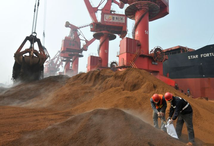 Chinesische Arbeiter nehmen Proben einer Eisenerz-Ladung