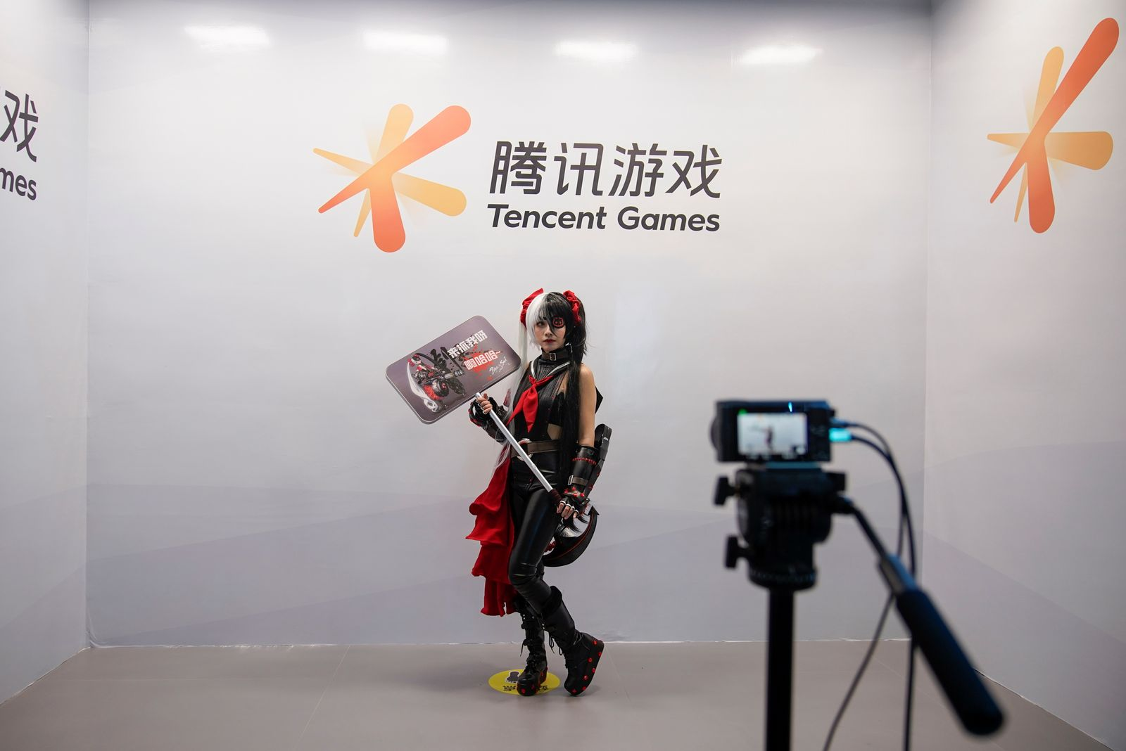 A cosplay fan poses for a photo at a Tencent Games booth during the China Digital Entertainment Expo and Conference, also known as ChinaJoy, in Shanghai