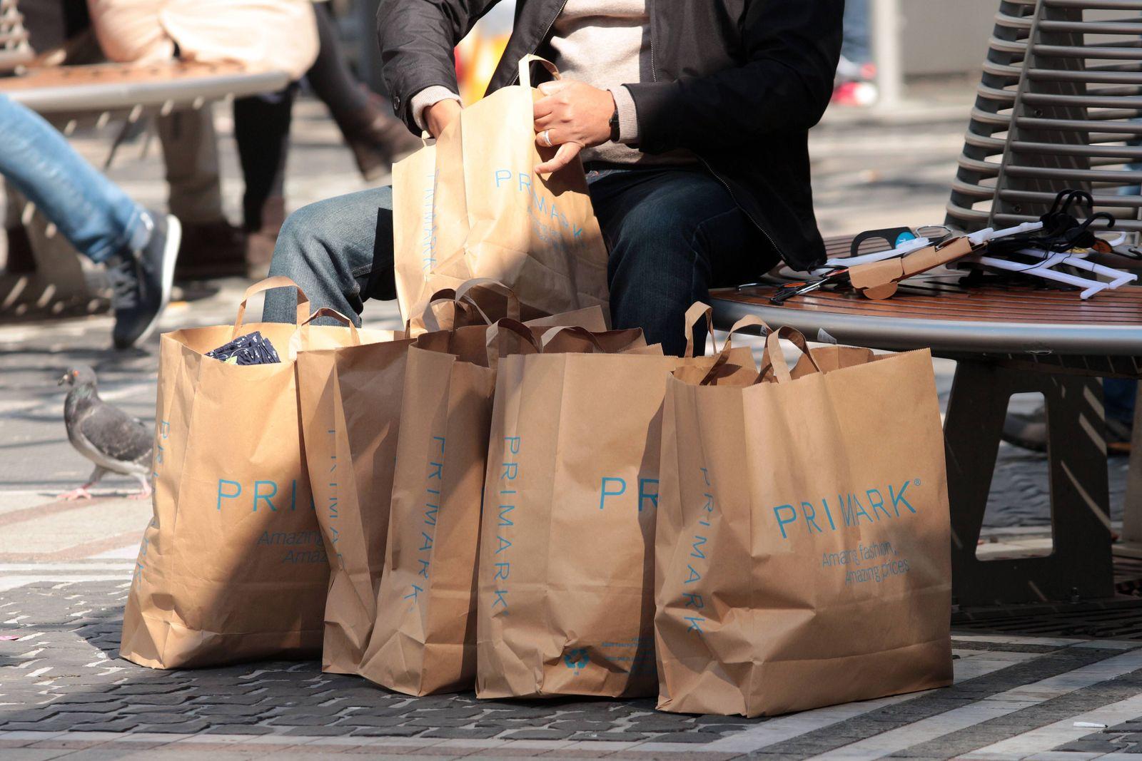 Mann sortiert seinen Großeinkauf in den vielen Einkaufstüten bei Primark in Frankfurt, Hessen, Deutschland