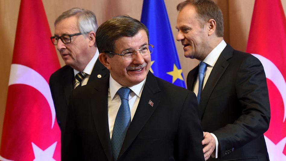 Türkeis Regierungschef Ahmet Davutoglu (mit Jean Claude Juncker und Donald Tusk): Die Türkei ist bereit, Flüchtlinge aus der EU zurückzunehmen - fordert aber mehr Geld als bislang zugesagt