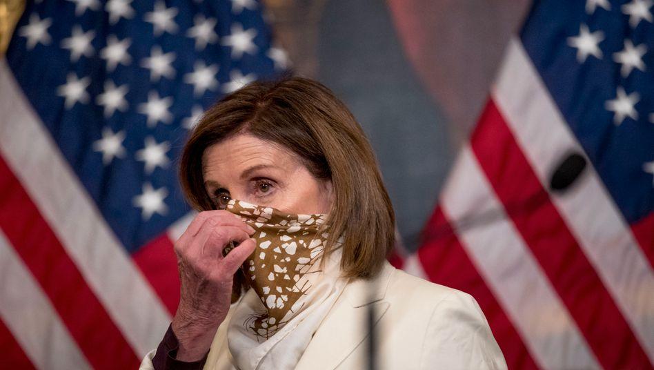 """Nancy Pelosi, Sprecherin des US-Repräsentantenhauses, zieht ihren Schal hoch, nachdem sie das """"Paycheck Protection Program"""" und den """"Health Care Enhancement Act"""" unterschrieben hat. Das weitere US-Konjunkturpaket in Höhe von 484 Milliarden US-Dollar lässt die US-Staathilfen auf mehr als 2,5 Billionen Dollar anwachsen."""