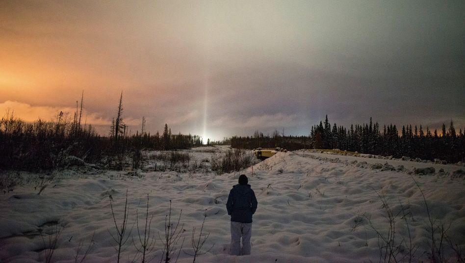 Verlorenes Land:Eine Cree-Ureinwohnerin schaut über einen Streifen Land bei Fort McMurray, der einst zum traditionellen Jagdrevier ihres Stammes gehörte. Im Hintergrund leuchten Anlagen für den Ölsandabbau.