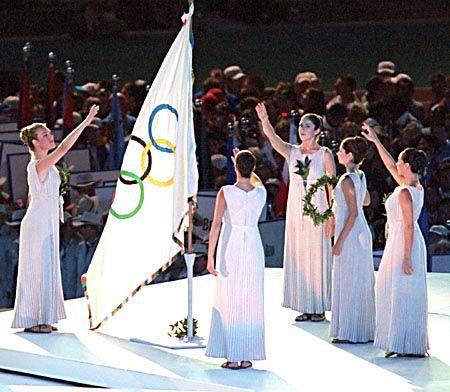Griechische Tempelfrauen ehren die Olympische Fahne, die an die Stadt Athen verliehen wurde, wo die Olympischen Spiele 2004 stattfinden werden.