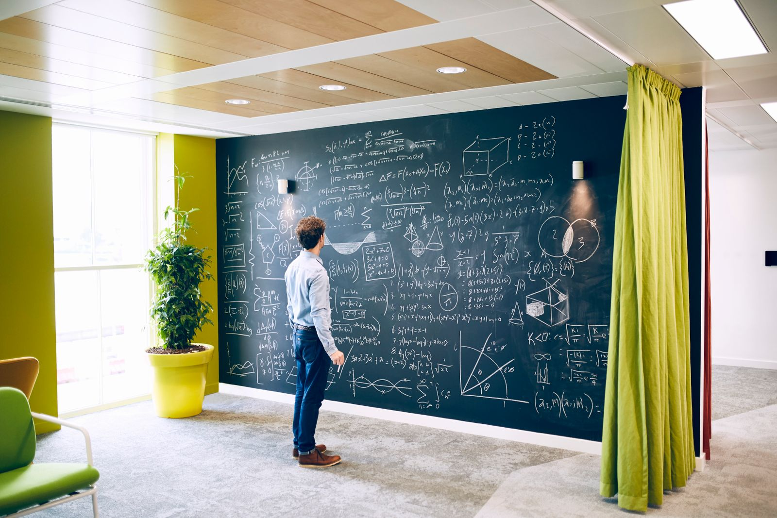 Businessman working with formula on wall