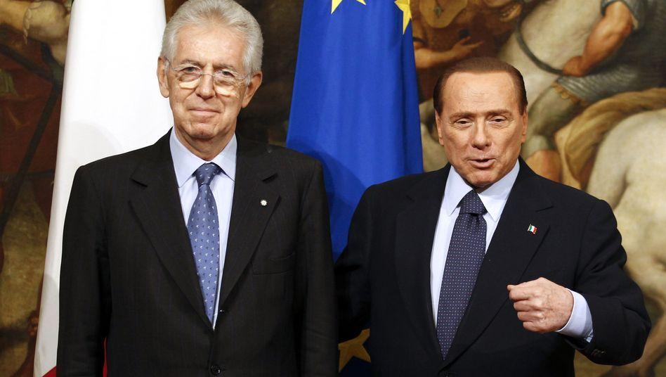 Newly appointed Prime Minister Mario Monti poses with his predecessor Silvio Berlusconi at Chigi palace in Rome