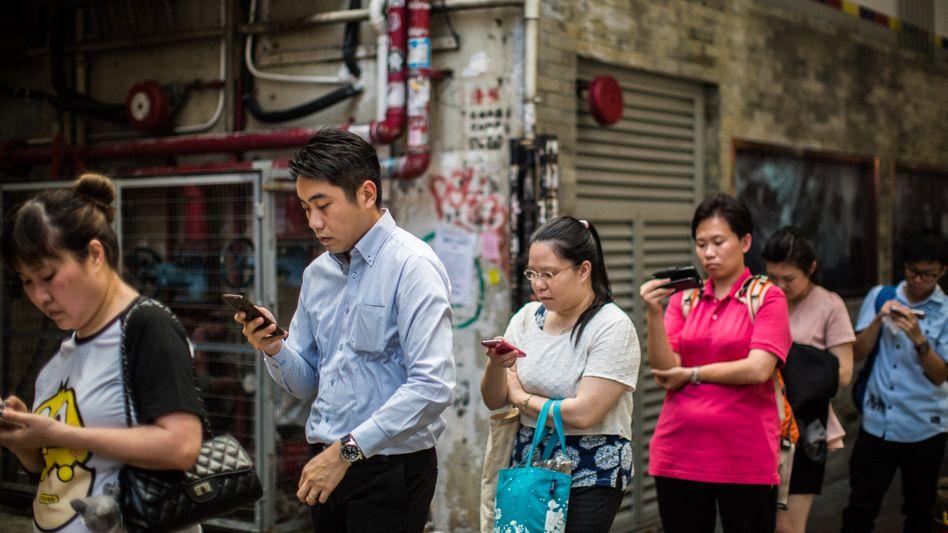 Mobiler Online-Alltag: Wartende an einer der Bushaltestelle in Hong-Kong