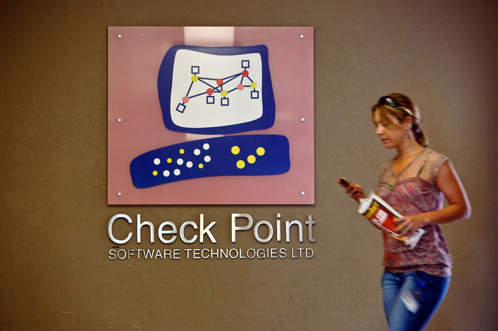 A woman walks past the Check Point Software Technologies Ltd. logo at the company's offices in Tel Aviv
