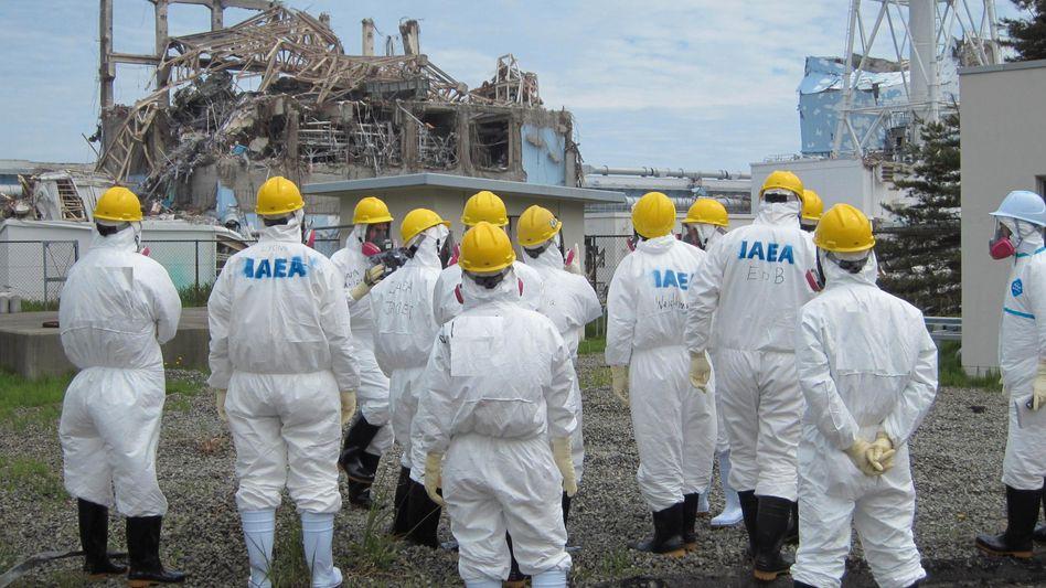 Ein Bild des Grauens: Mitarbeiter des Akw-Betreibers Tepco sowie Vertreter der Internationalen Energieagentur (IEA) auf dem Gelände des havarierten Meilers in Fukushima