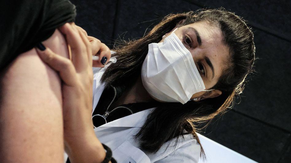Einer von 5,7 Millionen: Eine israelische Fachkraft verabreicht einem Mitbürger eine Corona-Impfung