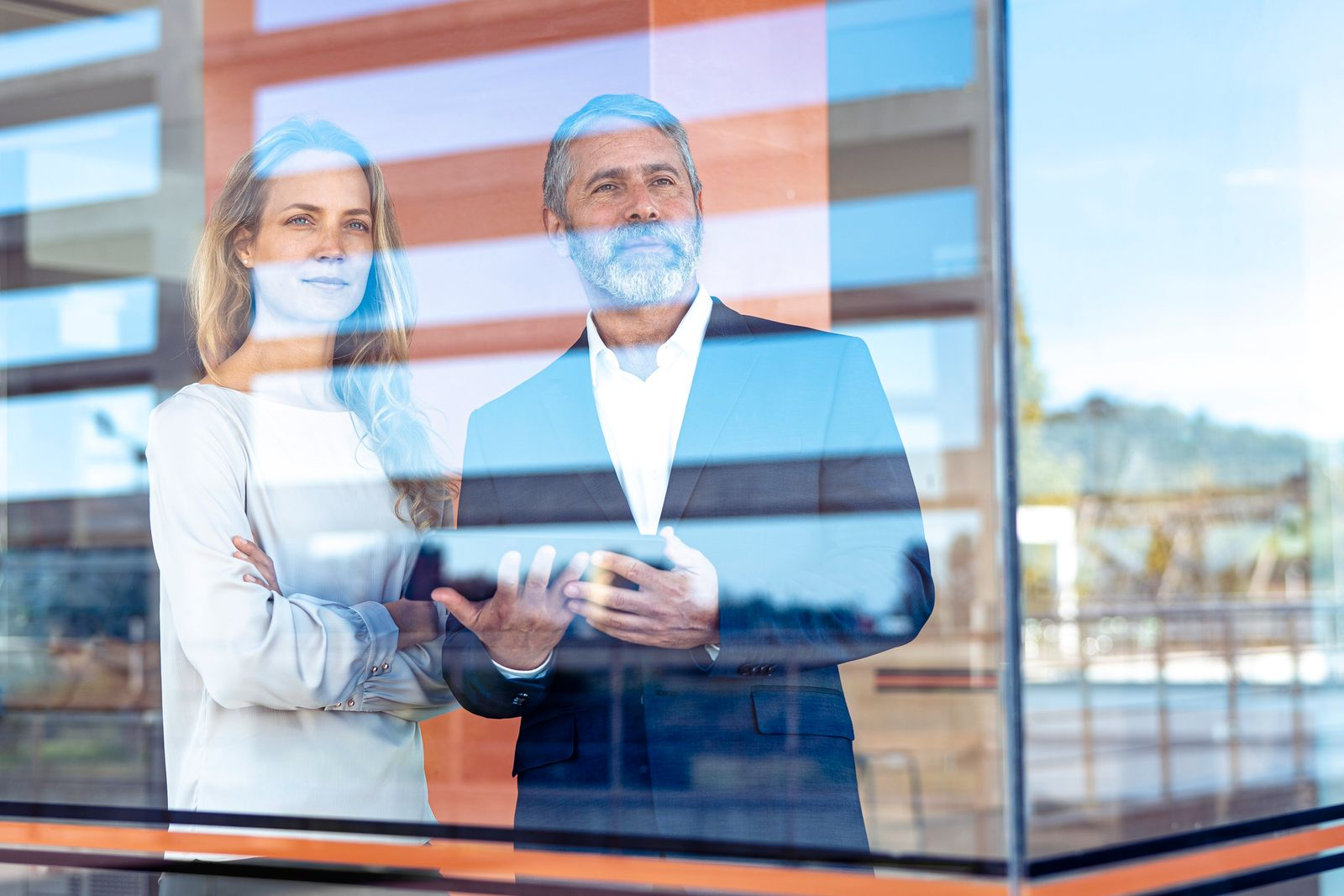 Confident professionals with digital tablet looking through window while standing at office