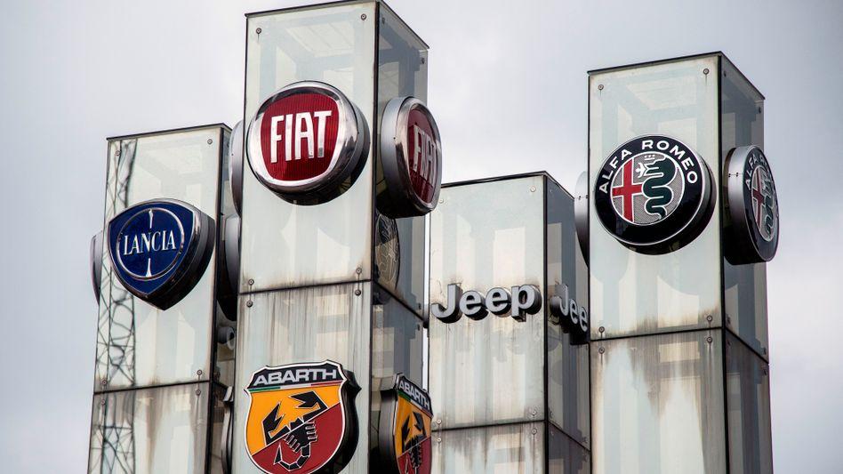 Logos der FCA-Marken Lancia, Fiat, Jeep und Alfa Romeo: Der Konzern führt nun mit PSA Fusionsgespräche