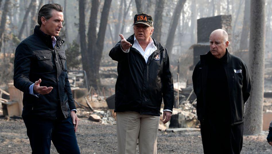Klimawandel, welcher Klimawandel? Donald Trump (Mitte) im November 2018 in einem abgebrannten Viertel eines Ortes in Kalifornien, der zu jener Zeit wie andere auch von schwersten Waldbränden heimgesucht worden war. Kaliforniens heutiger Gouverneur Gavin Newsom (links) und der heutige Ex-Gouverneur Jerry Brown (rechts) durften dem US-Präsidenten seinerzeit schon die Notwendigkeit schärferer Emissions- und Klimagesetze nahgelegt haben