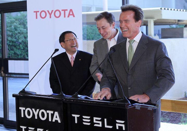 Toyota-Chef Akio Toyoda, Tesla-Chef Elon Musk und der damalige kalifornische Gouverneur Arnold Schwarzenegger (v.l.) lachen bei einer Konferenz am Tesla-Hauptsitz in Palo Alto kurz vor dem Börsengang.