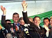 Gefeierte Retter: Bundeskanzler Gerhard Schröder und der ehemalige Holzmann-Chef Heinrich Binder (links) winken Ende November 1999 tausenden Holzmann-Beschäftigten zu. Im Frühjahr 2002 meldete der Bauriese Insolvenz an.