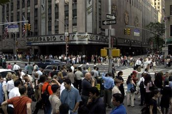 Fußgänger strömen über eine sonst von Autos verstopfte Kreuzung im Herzen Manhattans. Im Hintergrund die Radio City Music Hall, deren Neonröhren sonst Tag und Nacht leuchten.