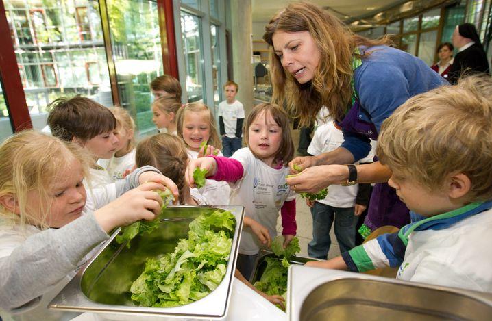 Wer mitmacht, weiß auch das Ergebnis zu würdigen: Starköchin Sarah Wiener beim Salatzupfen mit Kindern