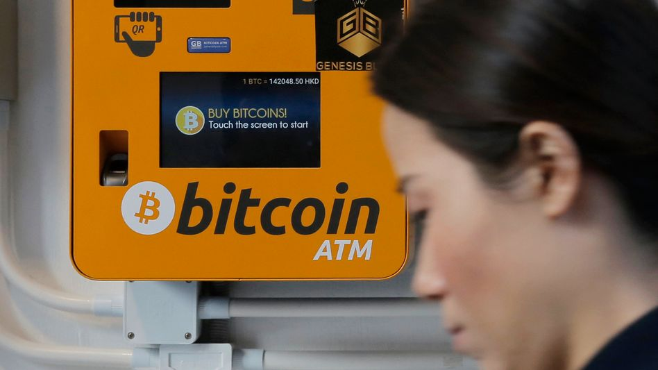 Frau an Bitcoin-Automat in Hongkong: Trotz der Kursschwäche ziehen Krypto-Währungen weiterhin Interesse auf sich.