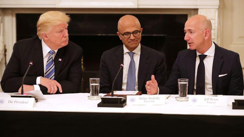 Politik und Milliardengeschäfte: US-Präsident trump (l.) mit Microsoft-CEO Satya Nadella (M.) und Amazon-Gründer Bezos