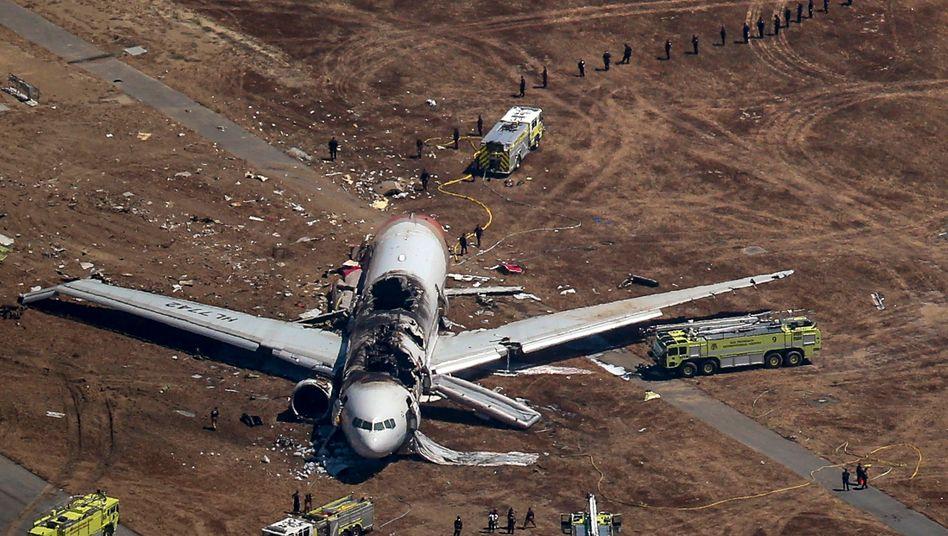 Bruchlandung: Die Boeing 777 liegt mit aufgerissener und verbrannter Kabinendecke auf dem Rollfeld, das Heck des Flugzeugs ist abgebrochen