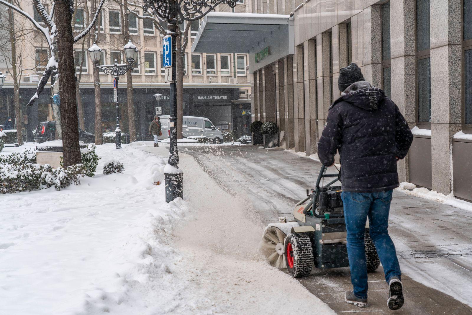 Privater Winterdienst, Schneefeger vor einem Geschäftshaus in der Innenstadt von Essen, Kettwiger Strasse, Wintereinbru