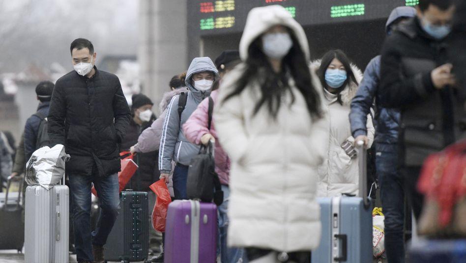 Reisende an einem Bahnhof in Peking