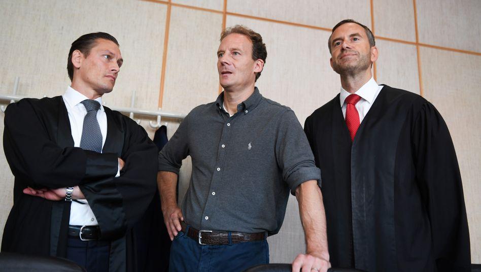 Alexander Falk (Mitte) zusammen mit seinen Verteidigern vor Gericht in Frankfurt (Archivaufnahme, 2019)
