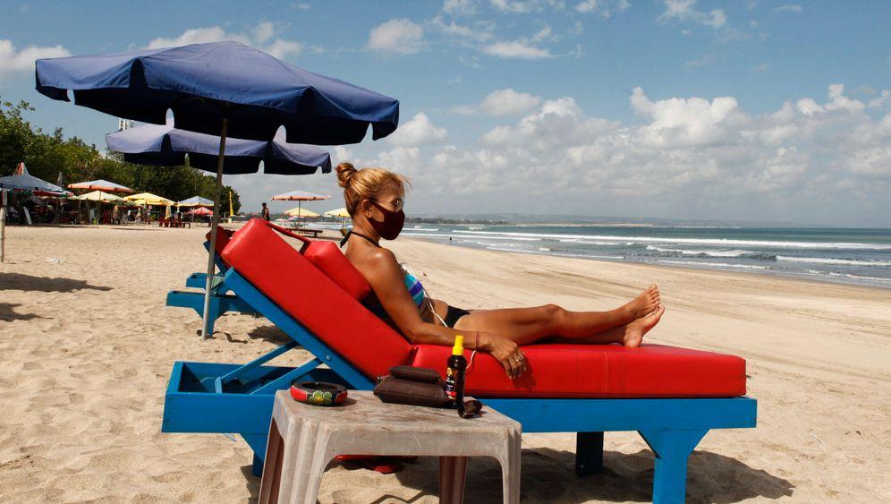 Touristin mit Mund-Nasenschutz auf Bali im Juli 2020: Die für die indonesische Insel so wichtige Tourismusbranche liegt wegen der Corona-Pandemie seit Monaten am Boden