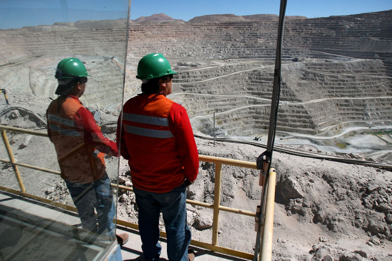 FILE PHOTO: Workers at BHP Billiton's Escondida, the world's biggest copper mine, are seen in front of the open pit, in Antofagasta,