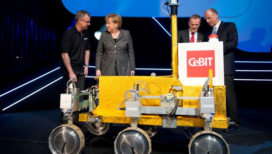 """Keine Dampflok: Bundeskanzlerin Angela Merkel, der Premier des Cebit-Partnerlands Polen, Donald Tusk, und EADS-Chef Thomas Enders (v. l.) bestaunen zur Eröffnung der weltweit größten Computermesse Cebit das Mars-Mobil """"Bridget"""""""