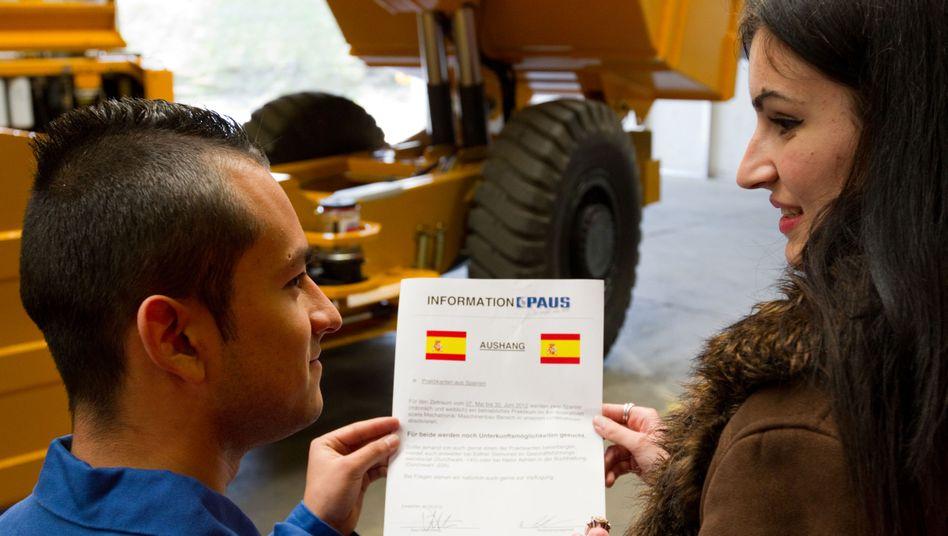 Spanische Auszubildende in Deutschland: Daniel Marín Carmona (l.) und Silvia Gómez Bernal blicken in ein Infoblatt. Im Kampf gegen den Fachkräftemangel wirbt auch das norddeutsche Wirtschaftsbündnis Ems-Achse um ausländische junge Menschen, die dann eine Lehre deutschen Betrieben abslolvieren