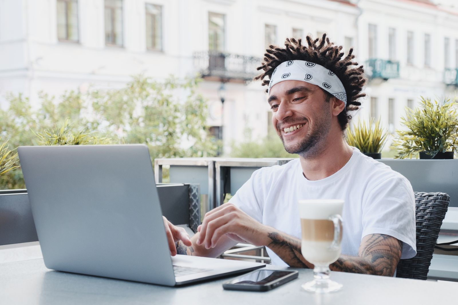 Happy Young Man Using Laptop While Sitting At Table