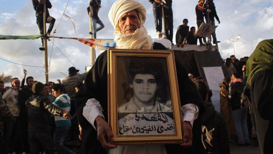 Protest in Benghasi: Ein Familienvater hält das Portrait seines Sohnes, der während der Proteste gegen Gaddafis Regime getötet wurde. Die Eu plant ein Waffenembargo sowie ein Exportverbot für bestimmte Güter