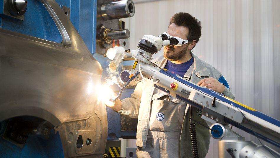 VW-Mitarbeiter mit Laser-Schweiß-Roboter: