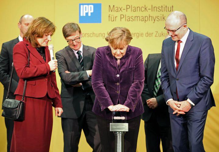 Auf Knopfdruck Energie: Merkel startet mit Institutsdirektorin Sybille Günter und Ministerpräsident Erwin Sellering den Kernfusionsreaktor Wendelstein 7-X in Greifswald ein