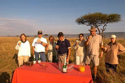 Nach der Landung gibt es die obligatorischen Taufe mit Champagner und danach ein einmaliges Frühstück mitten in der Savanne