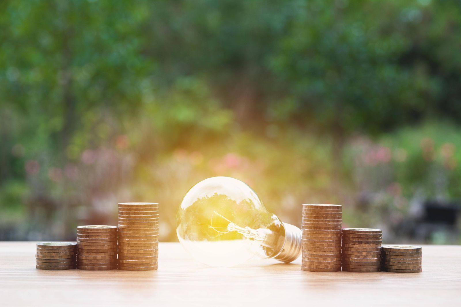 Energy saving light bulb with stacks of coins on nature background PUBLICATIONxINxGERxSUIxAUTxONLY