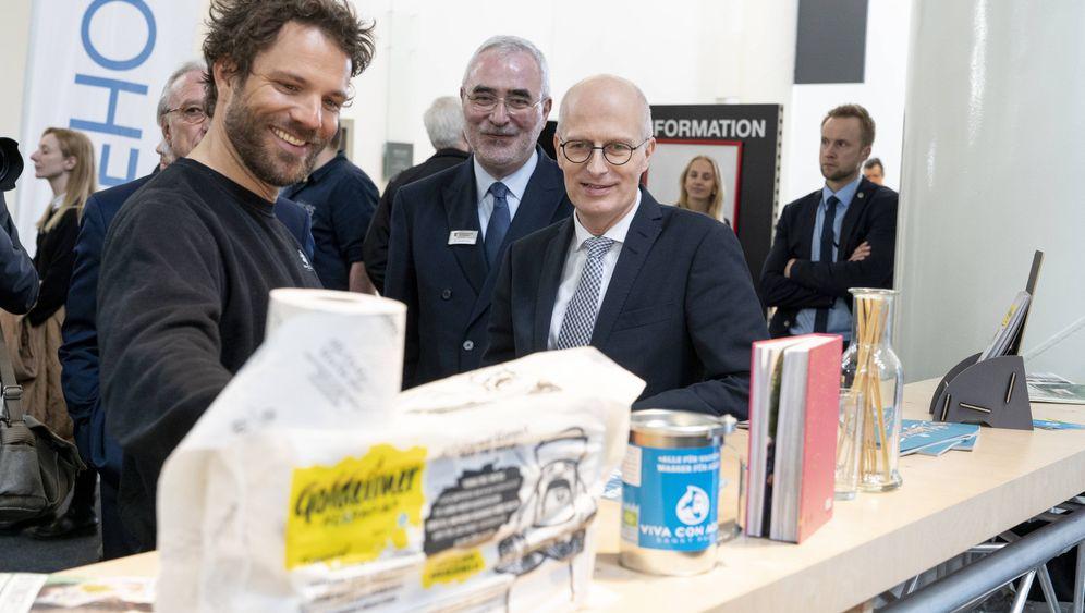 Spendensammler: Benjamin Adrion (l.) mit Hamburgs Erstem Bürgermeister Peter Tschentscher (M.) bei der Internorga-Messe mit Goldeimer-Toilettenpapier