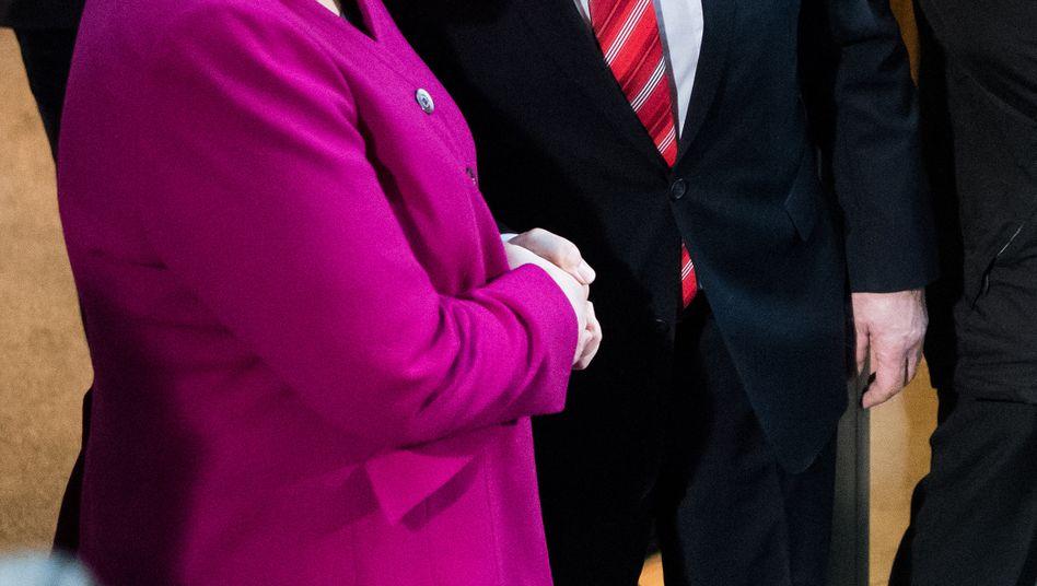 Bundeskanzlerin Angela Merkel und SPD-Vorsitzender Martin Schulz begrüßen einander beim Start der Sondierungsgespräche zwischen SPD, CDU und CSU im Willy-Brandt-Haus in Berlin.