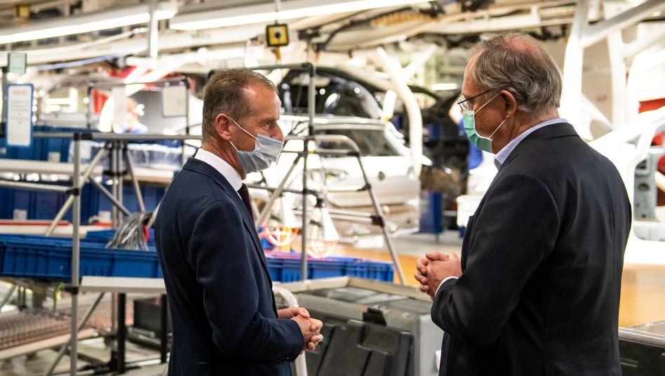 Langsam fährt VW die Produktion unter scharfen Auflagen wieder hoch. Doch die Nachfrage bleibt schwach, wie Volkswagen-Chef Herbert Diess aus jüngsten Absatzzahlen weiß (hier im Gespräch mit Niedersachsens Ministerpräsident Stephan Weil beim Re-Start der Fabrik in Wolfsburg)