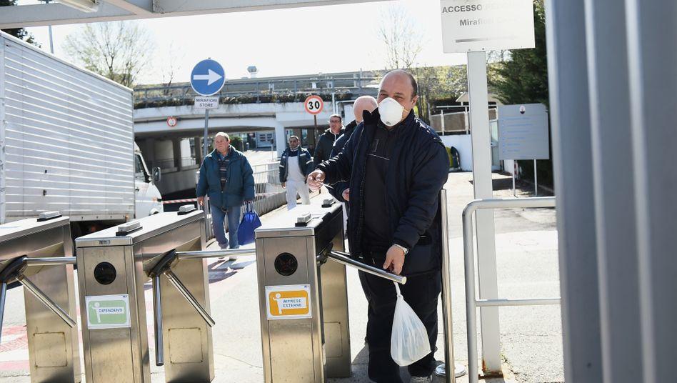 Jetzt sechs Fabriken allein in Italien geschlossen: Ein Fiat-Mitarbeiter mit Maske verlässt am 10. März eine Produktionsstätte in Turin.