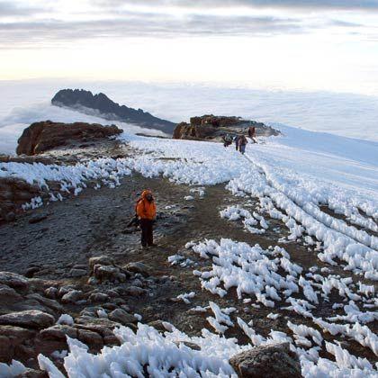 Sonnenaufgang am Kilimandscharo-Gipfel: Von der Eis- und Geröllwüste aus fällt der Blick auf eine dichte Wolkendecke, unter der sich die Savanne verbirgt
