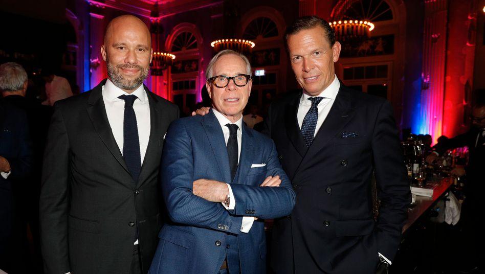 Doppelte Manndeckung: Oliver Timm (l.) wird Chief Sales Officer bei Hugo Boss und damit der wichtigste Mitarbeiter von Daniel Grieder (r.). Was Tommy Hilfiger (M.), hier noch in trauter Eintracht 2017 in Zürich, überhaupt nicht freut.