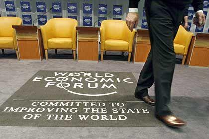 Wirtschaft gewinnt an Fahrt:Manager neben dem Logo des Weltwirtschaftsforums
