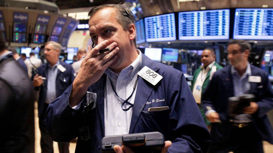 """Finanzmärkte in Aufruhr: Die Drohung von Standard & Poor's, die gesamte Euro-Zone herabzustufen, setzt die Aktienkurse unter Druck. S&P setze den """"Währungskrieg"""" fort, meinen Kritiker"""