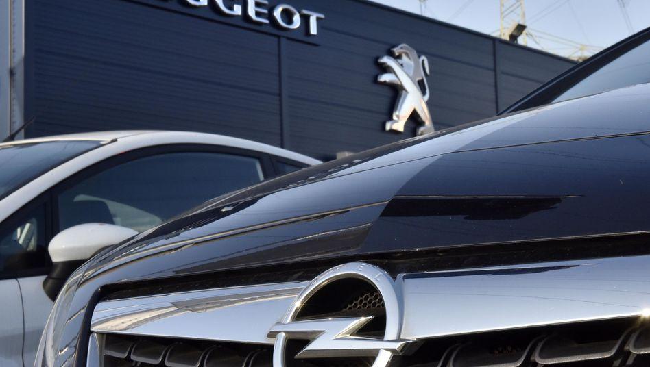 Opel-Auto vor einem Peugeot-Logo: Bis Jahresende will Peugeot die Übernahme von Opel abschließen