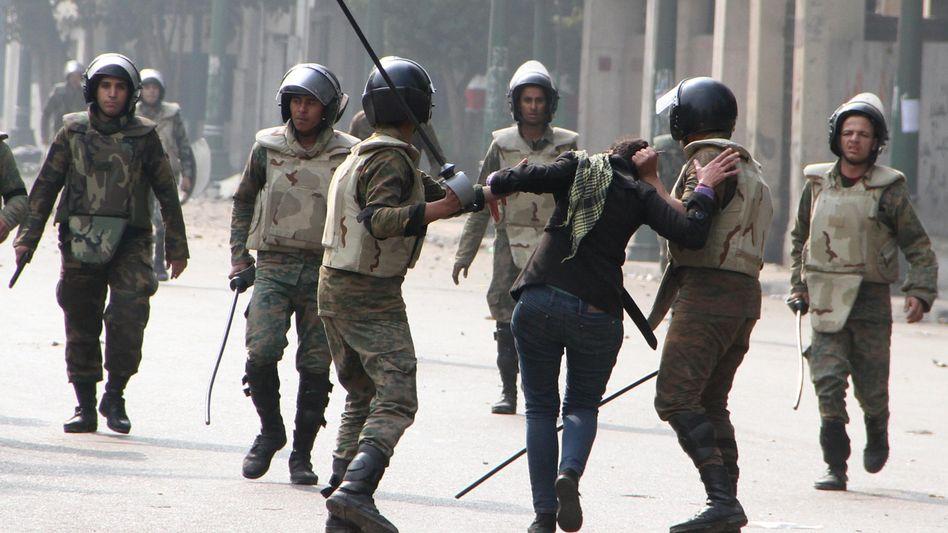 Der Aufstand geht weiter: Ägyptische Polizisten verhaften eine Demonstrantin in Kairo