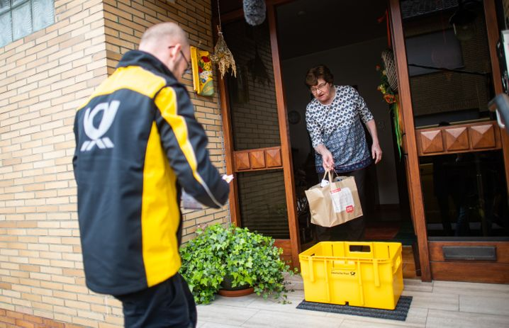 Zusteller der Post beliefern Kunden in Quarantäne auch schon mal mit Lebensmittel in Postboxen. Der Konzern will seine 80.000 Brief- und 50.000 Paketzusteller aber nicht mit Masken ausstatten.
